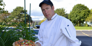 executive chef holding pizza